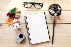 Escritorio del espacio de trabajo con el cuaderno, el lápiz, los conos del pino en taza de madera del té, los vidrios del ojo, la Fotos de archivo libres de regalías