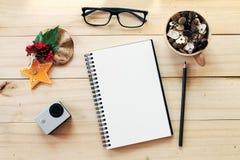Escritorio del espacio de trabajo con el cuaderno, el lápiz, los conos del pino en taza de madera del té, los vidrios del ojo, la Imagenes de archivo
