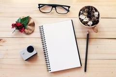 Escritorio del espacio de trabajo con el cuaderno, el lápiz, los conos del pino en taza de madera del té, los vidrios del ojo, la Fotos de archivo