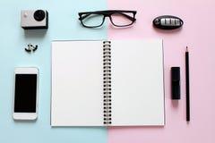 Escritorio del espacio de trabajo con el cuaderno en blanco, el lápiz, el lápiz labial, la llave del coche, los vidrios del ojo,  Fotografía de archivo libre de regalías