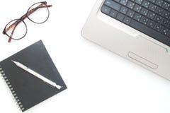 Escritorio del espacio de trabajo con el ordenador portátil, el cuaderno y las lentes encendido Imagenes de archivo