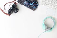 Escritorio del espacio de trabajo con el ordenador portátil, la cámara, los auriculares y woma Imagen de archivo