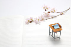 Escritorio del estudio, libro azul y flores de cerezo fotos de archivo libres de regalías