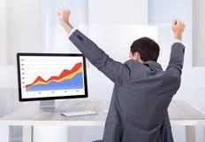 Escritorio del ordenador de Celebrating Success At del hombre de negocios Imagen de archivo libre de regalías