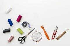 Escritorio del trabajo del ` s del sastre Modelo de accesorios y de herramientas de costura en el copyspace blanco de la opinión  Imágenes de archivo libres de regalías