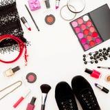 Escritorio femenino con los cosméticos, los accesorios y los zapatos en el fondo blanco Endecha plana, visión superior fotografía de archivo libre de regalías