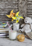 Escritorio nacional del trabajo del niño con los libros, los cuadernos, las libretas, el vidrio de leche y un bollo Fotografía de archivo libre de regalías