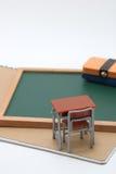Escritorio, pizarra y cuaderno miniatura de la escuela en el fondo blanco Fotos de archivo libres de regalías