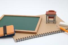 Escritorio, pizarra y cuaderno miniatura de la escuela en el fondo blanco Imagenes de archivo