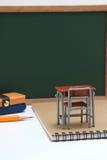 Escritorio, pizarra y cuaderno miniatura de la escuela en el fondo blanco Foto de archivo