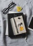 Escritorio plano del ` s de las mujeres de la endecha con la tableta, libreta, teléfono, vidrios, auriculares En un fondo gris, v Imagen de archivo libre de regalías