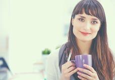 Escritorio que hace una pausa del diseñador de moda atractivo joven en la oficina, sosteniendo la taza Imagen de archivo libre de regalías
