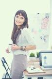Escritorio que hace una pausa del diseñador de moda atractivo joven en la oficina, sosteniendo la taza Foto de archivo
