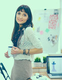 Escritorio que hace una pausa del diseñador de moda atractivo joven en la oficina, sosteniendo la taza Fotografía de archivo libre de regalías