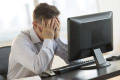 Escritorio subrayado de Leaning On Computer del hombre de negocios Fotografía de archivo libre de regalías