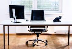 Escritorio vacío moderno del espacio de oficina con el ordenador, el teléfono y la silla imagenes de archivo