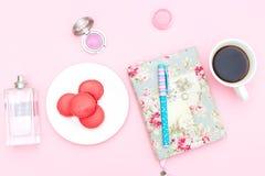 Escritorio y accesorios femeninos en un fondo rosado Brea del café Fotografía de archivo