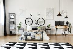 Escritorio y bicicleta en dormitorio Fotografía de archivo libre de regalías