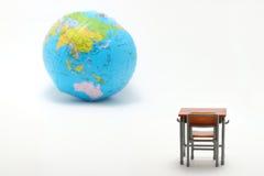 Escritorio y globo miniatura del estudio de la escuela en el fondo blanco Fotos de archivo libres de regalías
