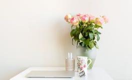 Escritorio y rosas rosadas Fotografía de archivo
