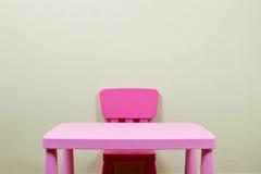 Escritorio y silla de los cabritos contra la pared foto de archivo