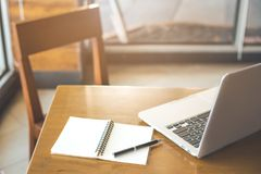 Escritorio y silla de madera con la libreta Plumas y ordenadores portátiles Fotos de archivo
