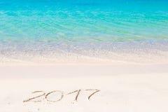 2017 escritos à mão no Sandy Beach com a onda de oceano macia no fundo Foto de Stock