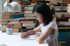 Escritura adolescente asiática joven en cuaderno Imágenes de archivo libres de regalías