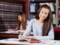 Escritura adolescente de la colegiala en libro en la tabla Foto de archivo
