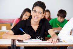 Escritura adolescente del colegial en carpeta en el escritorio Fotografía de archivo libre de regalías