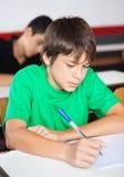 Escritura adolescente del colegial en el escritorio durante Fotografía de archivo