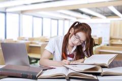 Escritura adolescente del estudiante en el libro en clase Imagen de archivo libre de regalías