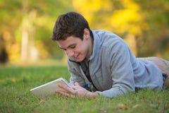Escritura adolescente feliz en hierba Imagenes de archivo