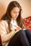 Escritura adolescente morena de la muchacha en diario en el dormitorio Fotografía de archivo