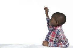 Escritura africana del muchacho con el lápiz, espacio de la copia libre Imagenes de archivo
