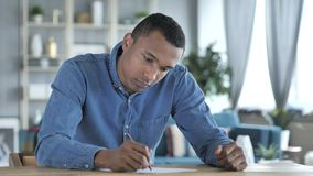 Escritura africana joven del hombre en los documentos en oficina, papeleo almacen de video