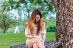 Escritura asiática de la mujer en el libro en un jardín o un parque Imagen de archivo