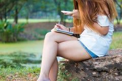 Escritura asiática de la mujer en el libro y smartphone el jugar en el parque Foto de archivo