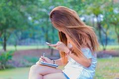 Escritura asiática de la mujer en el libro y smartphone el jugar en el parque Imagenes de archivo