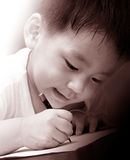 Escritura asiática del muchacho en el papel Imagenes de archivo