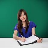Escritura asiática feliz del estudiante en el cuaderno, en fondo verde Fotografía de archivo libre de regalías