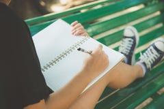 Escritura asiática joven de la mujer del inconformista feliz en su diario en parque imagen de archivo libre de regalías