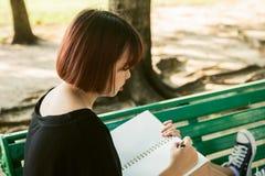 Escritura asiática joven de la mujer del inconformista feliz en su diario en parque fotos de archivo libres de regalías
