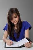 Escritura asiática joven de la mujer en el cuaderno Imágenes de archivo libres de regalías