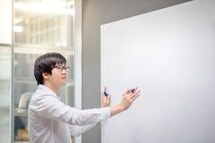 Escritura asiática joven del hombre en el tablero blanco en sala de reunión Fotografía de archivo