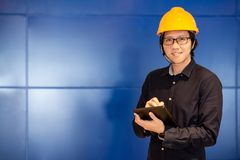 Escritura asiática joven del hombre del ingeniero en la tableta Foto de archivo