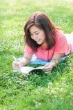 Escritura asiática joven feliz de la mujer en cuaderno y la sonrisa Imagen de archivo libre de regalías