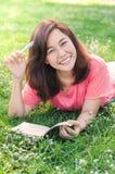 Escritura asiática joven hermosa de la mujer en su cuaderno en el prado Foto de archivo libre de regalías