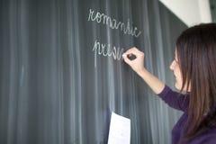 Escritura bastante joven del estudiante en la pizarra Fotos de archivo