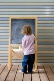 Escritura caucásica joven linda del muchacho en una pizarra Fotos de archivo libres de regalías